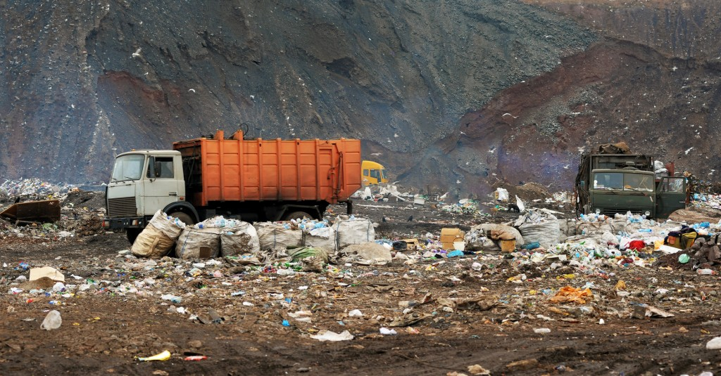 Garbage truck unloading at the dump indicating the need of Chicago environmental lawyers